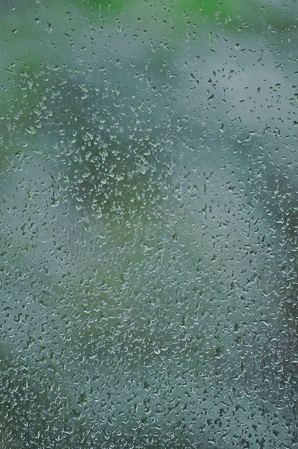 Regnig dag regndroppar på vått fönsterexponeringsglas, ljus lodlinje royaltyfria bilder