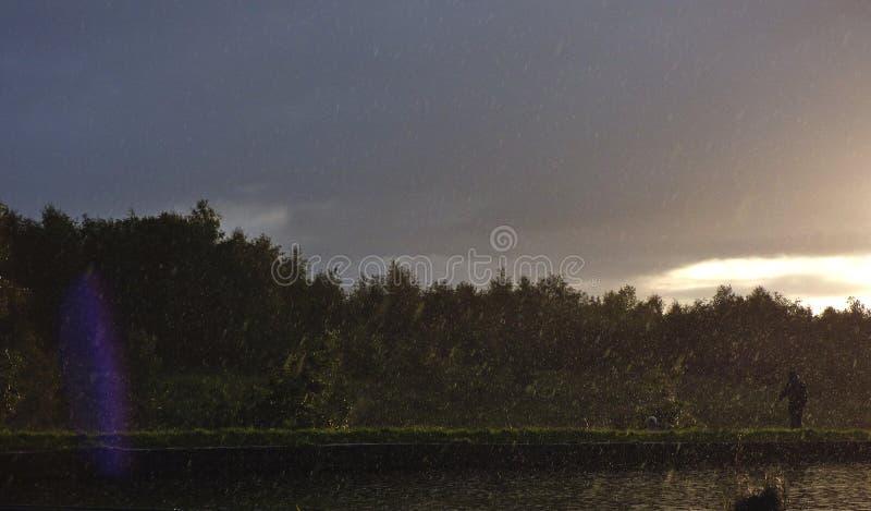 Regnig eftermiddag - regn startade att hälla ner bredvid kanalen med solen som skiner i avståndet, fotoet som togs i UK royaltyfri foto