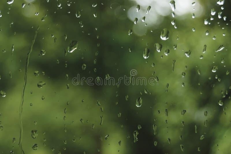 Regnig sommardag regndroppar på vått fönsterexponeringsglas, horisontalljus abstrakt detalj för modell för bakgrund för regnvatte arkivbild