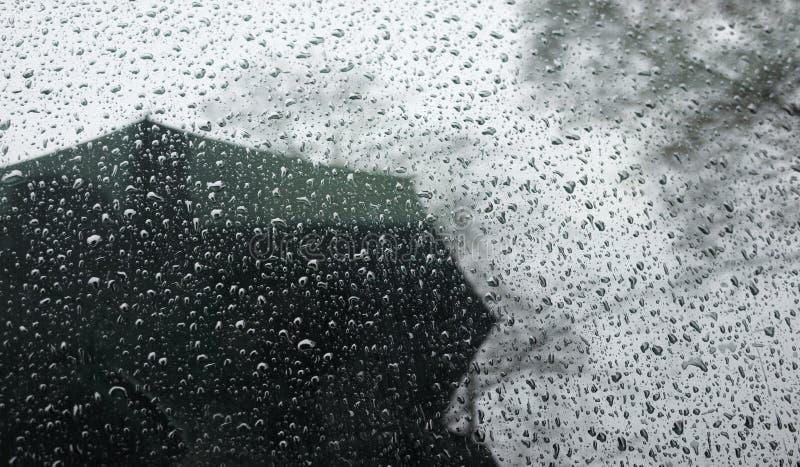 regniga väderreflexioner i bilfönster man med ett paraply under regn Dåligt väder arkivbilder