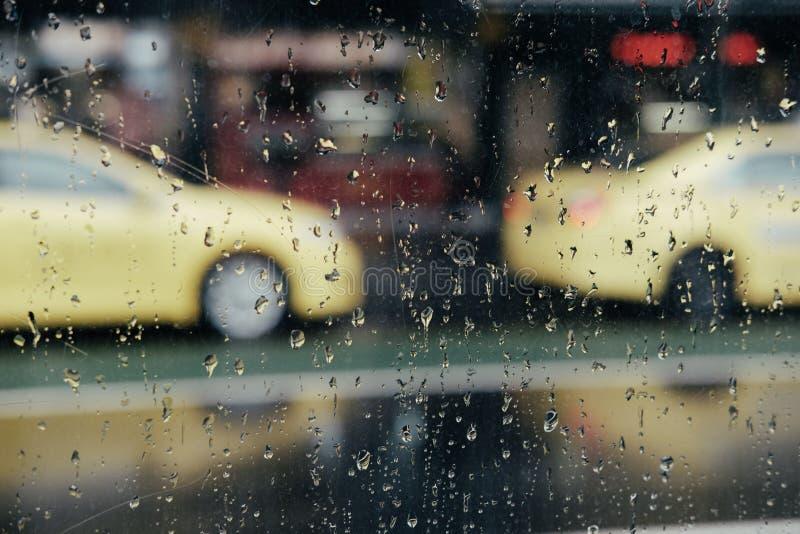 Regnigt f?nster med taxibilar som g?ras suddig i bakgrund royaltyfria foton