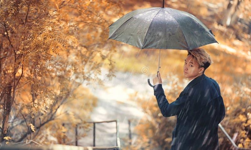 Regnigt väder för höst och en ung man med ett paraply royaltyfri foto