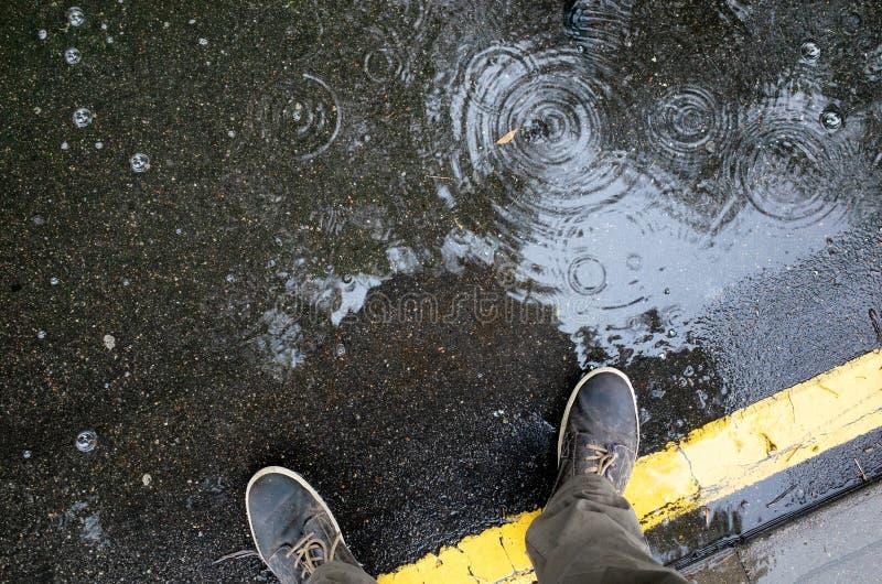 regnigt väder Mannen lägger benen på ryggen i gymnastikskor eller kängor som går till och med regnpölen på asfaltvägen, bästa sik royaltyfri foto