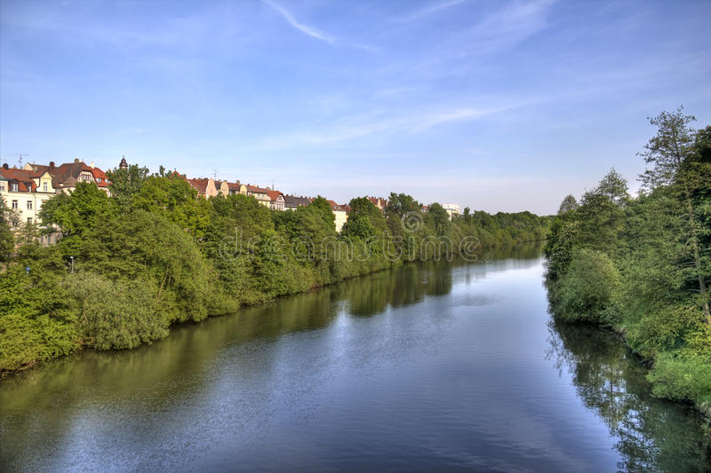 Regnitz river in Bamberg, Germany. The Regnitz river flanked by trees and historical houses in Bamberg, Germany royalty free stock image