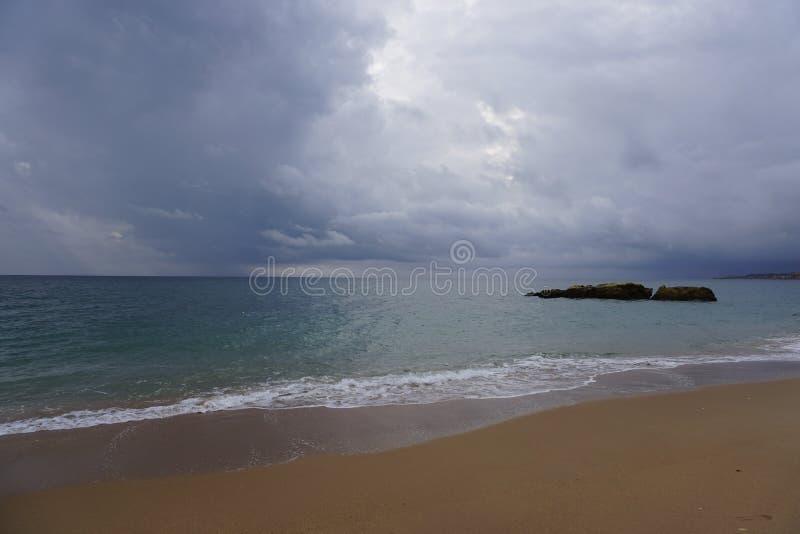 Regnmoln över havet athwart Blöta sand av stranden Bränningvågor och svart vaggar royaltyfri foto