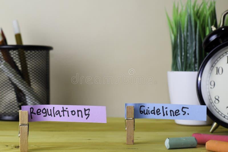 Regolamenti e linee guida Scrittura sulle note appiccicose in mollette sulla scrivania di legno fotografia stock