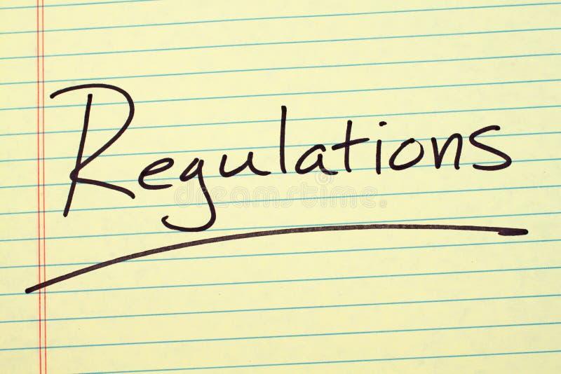Regolamenti su un blocco note giallo immagini stock libere da diritti