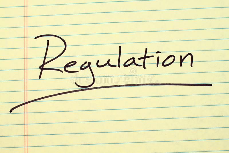 Regolamento su un blocco note giallo immagine stock libera da diritti