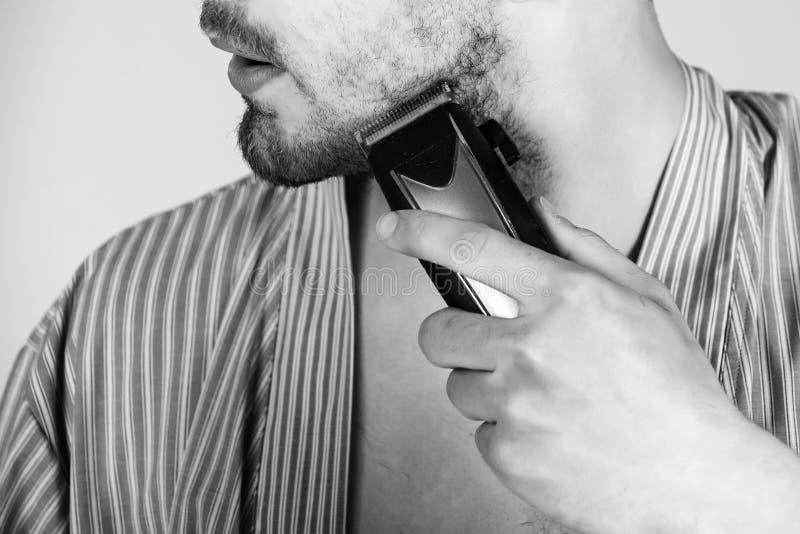 Regolatore della barba Mano con il rasoio elettrico o il rasoio che rade barba immagini stock