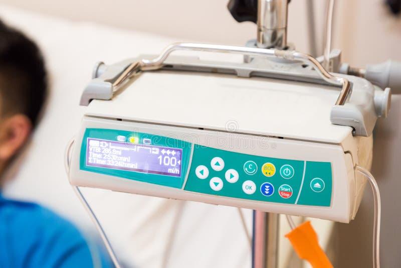 Regolatore della pompa per infusione IV con il paziente a fondo fotografia stock