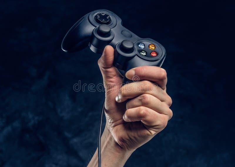 Regolatore di console del video gioco in mano del gamer contro lo sfondo della parete scura immagine stock