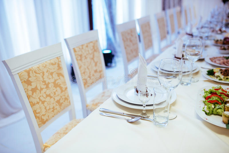 Regolazione alla moda convenzionale su una tavola di cena con cristalleria elegante fotografie stock