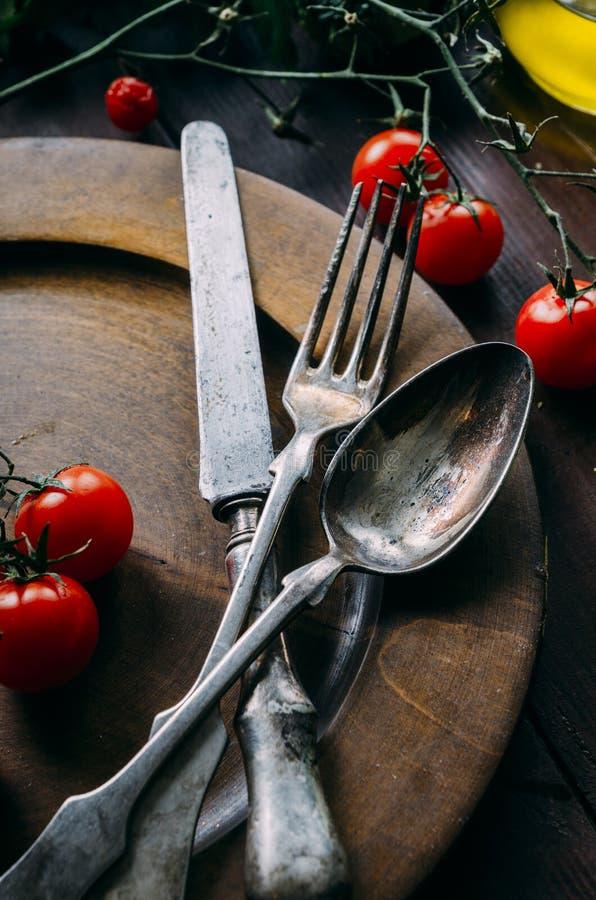 Regolazione d'annata della tavola con il vecchi cucchiaio d'argento, forchetta e coltello in piatto di legno scuro da sopra Cena  fotografia stock libera da diritti