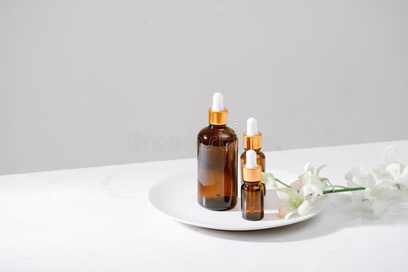 Regolazione della stazione termale con le orchidee e l'olio essenziale in una bottiglia di vetro, concetto di aromaterapia fotografie stock libere da diritti
