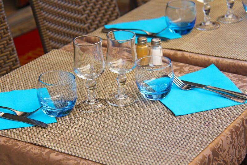 Regolazione della Tabella - coltello e forcella, calici di vetro, tovaglioli blu sulla b immagine stock libera da diritti