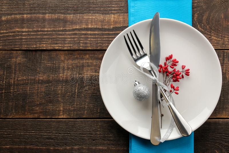 Regolazione della tabella di natale Coltello, forcella e piatto con il tovagliolo blu Su una tavola di legno marrone vista superi immagine stock
