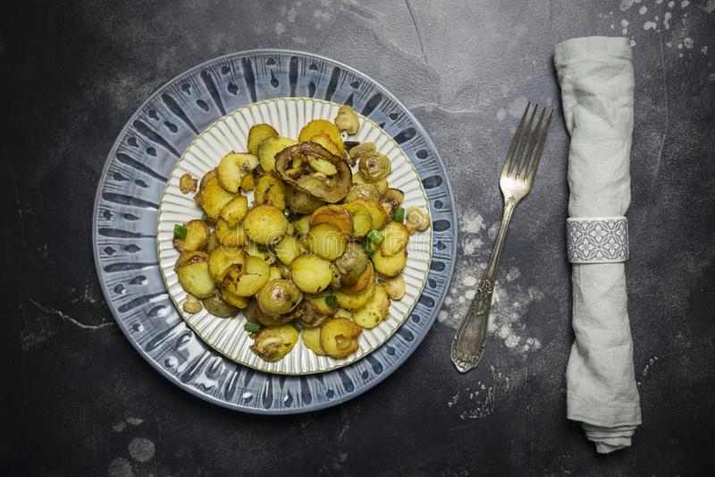 Regolazione della Tabella per la cena di festa Patate fritte con i funghi e la cipolla in piatto bianco a fondo nero Forcella e t fotografia stock libera da diritti