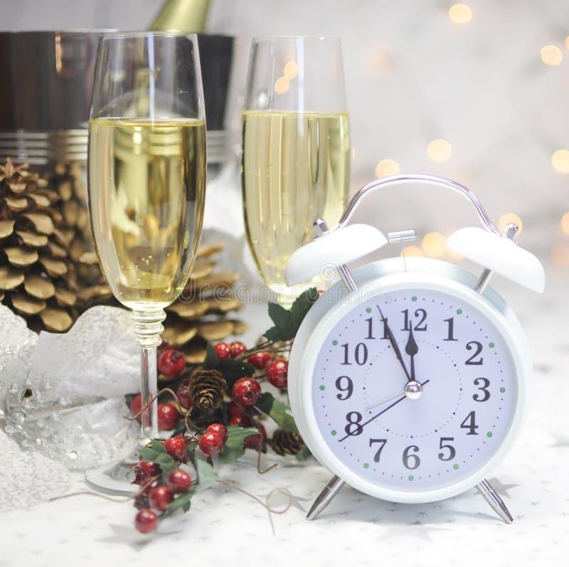 Regolazione della tavola del buon anno con il retro orologio bianco che mostra cinque alla mezzanotte fotografie stock