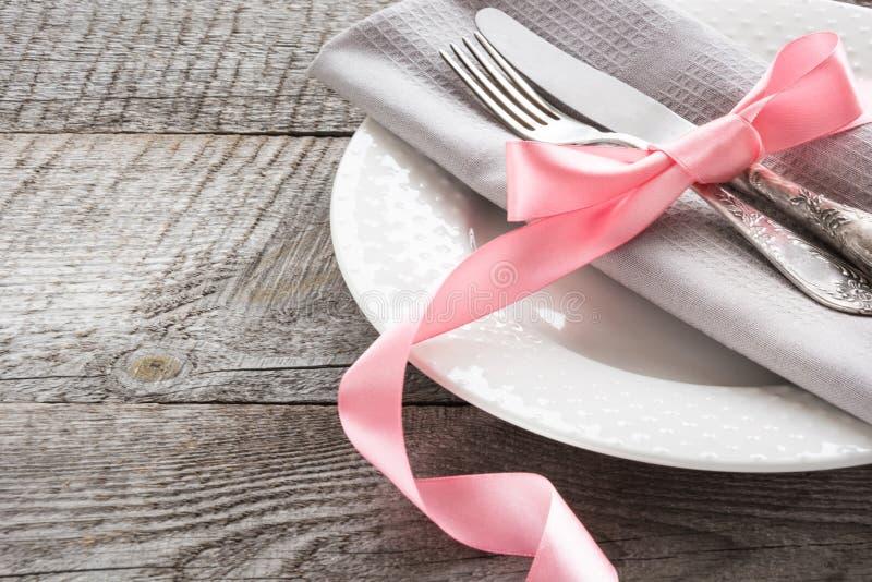 Regolazione della tavola di eleganza con il nastro rosa per la cena romantica sul bordo di legno Fine in su immagini stock libere da diritti