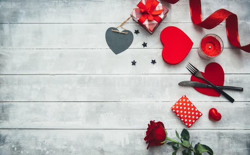 Regolazione della tavola di giorno di biglietti di S. Valentino con la forcella, il coltello, i cuori rossi, il nastro e le rose fotografie stock libere da diritti