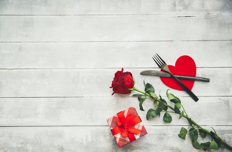 Regolazione della tavola di giorno del ` s del biglietto di S. Valentino con la forcella, il coltello, i cuori rossi, il nastro e fotografia stock