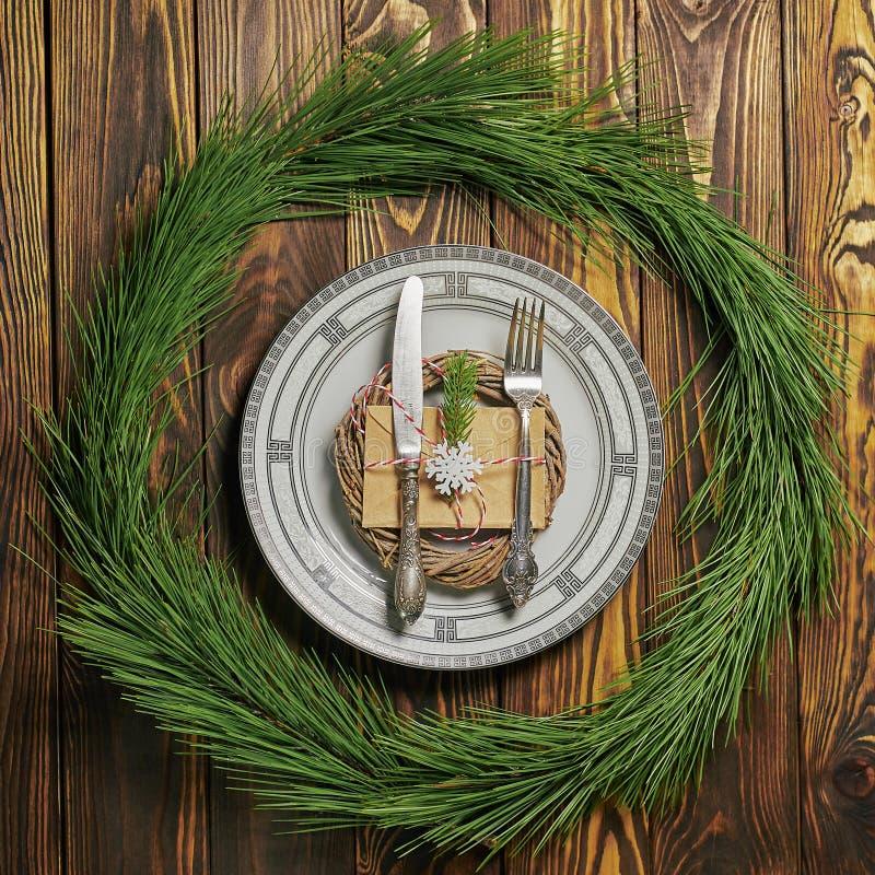 Regolazione della tavola di Natale al fondo di legno marrone con il piatto bianco, la coltelleria d'argento e la busta della cart immagine stock