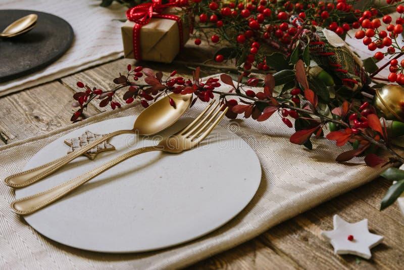 Regolazione della tavola di Natale, coltelleria dorata e corona dei nandinas fotografie stock libere da diritti
