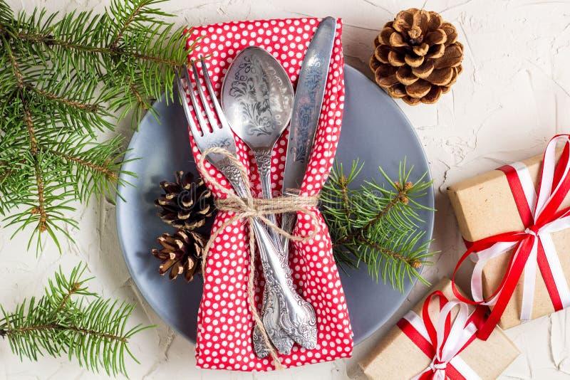 Regolazione della tavola di Natale con il bastoncino di zucchero, l'albero di Natale, le pigne ed il regalo, sulla tavola bianca, fotografia stock libera da diritti