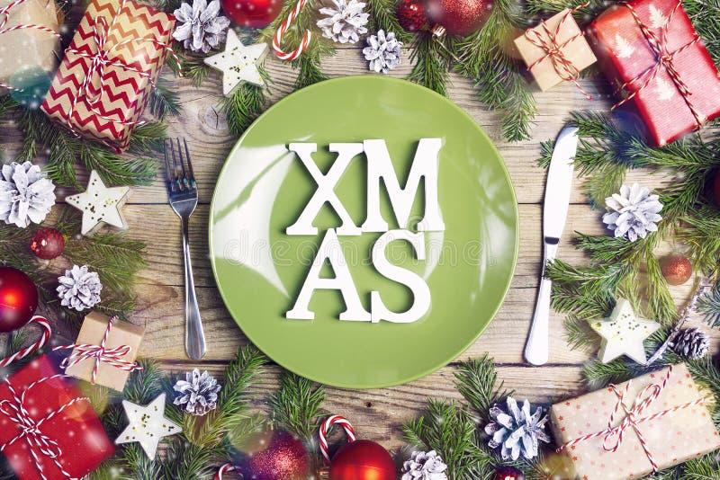 Regolazione della tavola di Natale con la coltelleria, le decorazioni ed i contenitori di regalo sulla tavola di legno fotografia stock