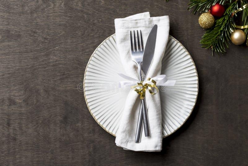 Regolazione della tavola di Natale con le decorazioni della forcella e del coltello e di natale sul piatto Fondo, fine su, spazio immagini stock