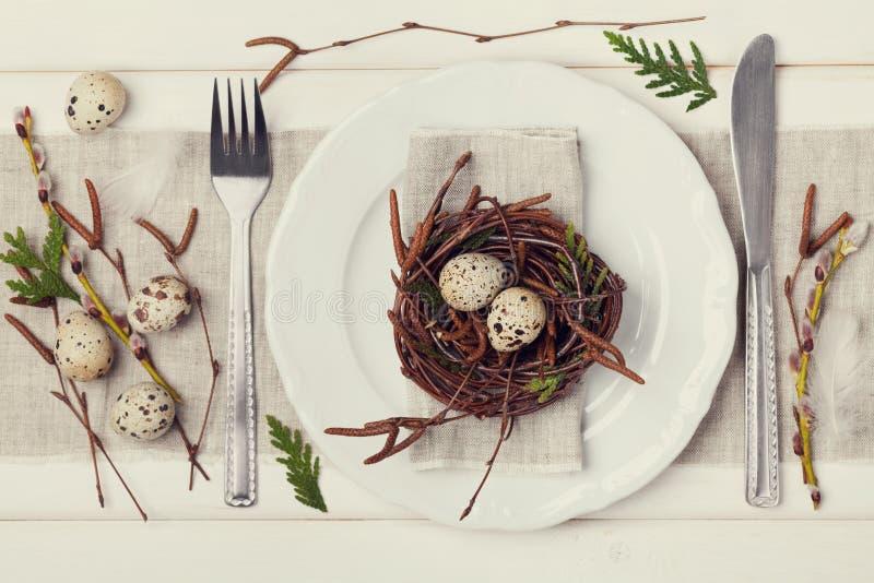 Regolazione della tavola di Pasqua con le uova e decorazione della molla su fondo rustico, tonalità d'annata immagini stock libere da diritti