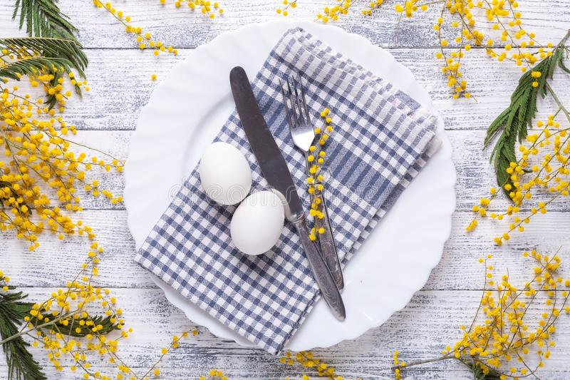 Regolazione della tavola di Pasqua Uova bianche, tovagliolo su un piatto, fiori della mimosa, forcella, coltello su una tavola di fotografia stock