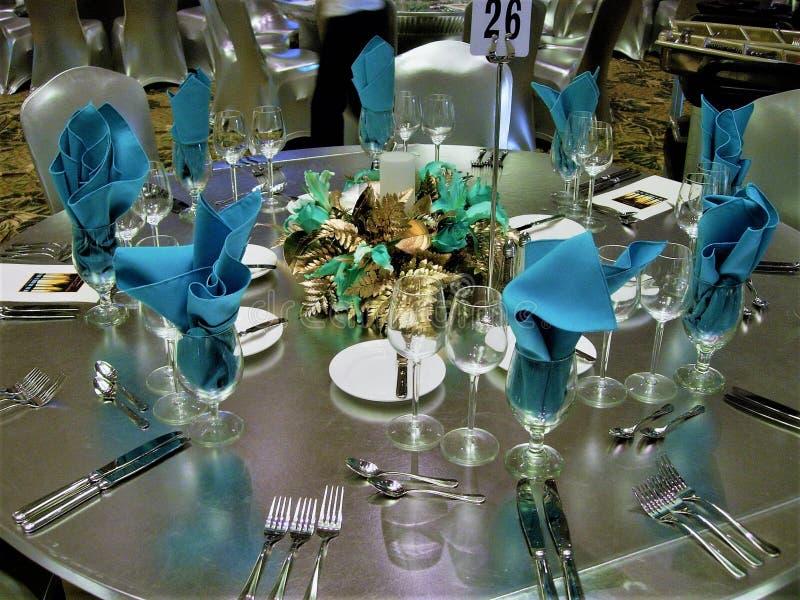 Regolazione della tavola della sala da ballo con la copertura di tavola dell'elastam, il centro blu ed i tovaglioli blu fotografia stock libera da diritti