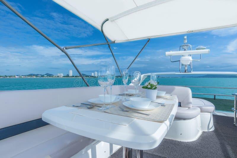 Regolazione di lusso della tavola del pranzo su un interno dell'yacht immagini stock