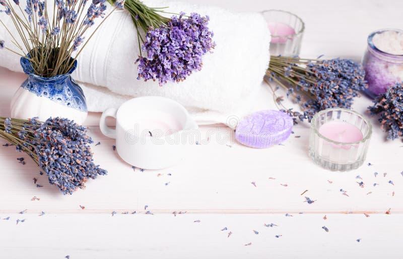 Regolazione di massaggio della stazione termale, prodotto della lavanda, sale, candele, sapone su fondo bianco fotografia stock