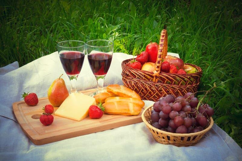 Regolazione di picnic con i vetri di vino rosso, di formaggio e dei frutti immagine stock