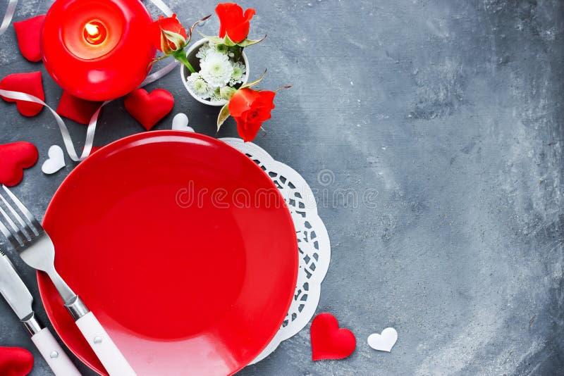 Regolazione di posto della tavola di giorno di biglietti di S. Valentino con il piatto rosso vuoto, coltello, fotografie stock