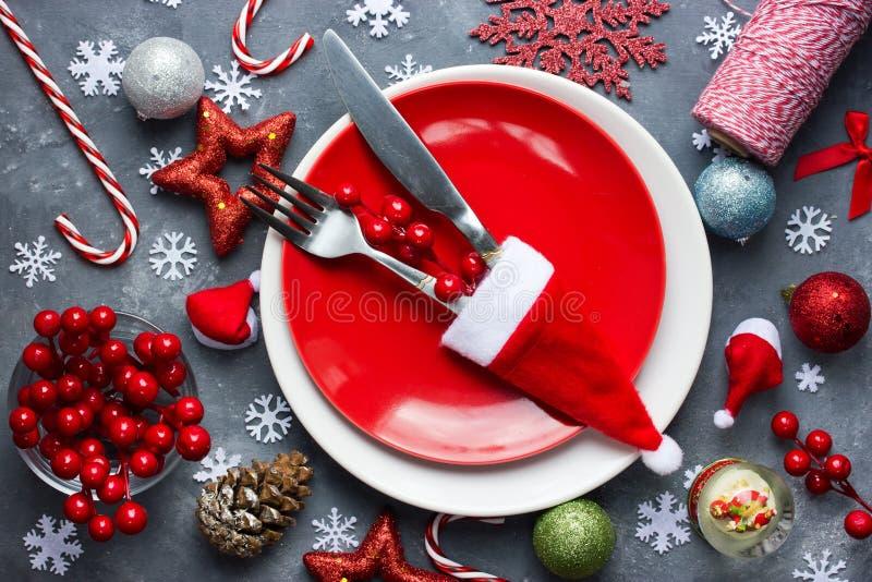 Regolazione di posto della tavola di Natale con il piatto rosso, coltelleria in Santa h fotografia stock libera da diritti