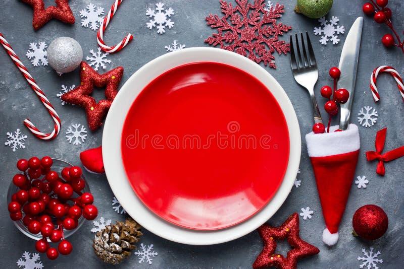 Regolazione di posto della tavola di Natale con il piatto rosso vuoto, coltelleria nella s immagine stock libera da diritti