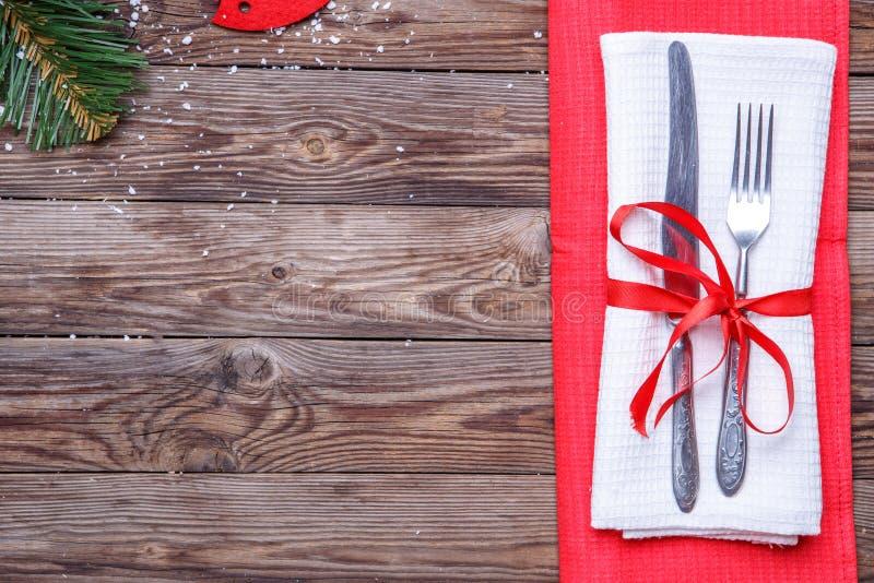 Regolazione di posto della tavola di Natale con la forcella e coltello, nastro ed arco rosso decorato e tovaglioli rossi e bianch fotografia stock