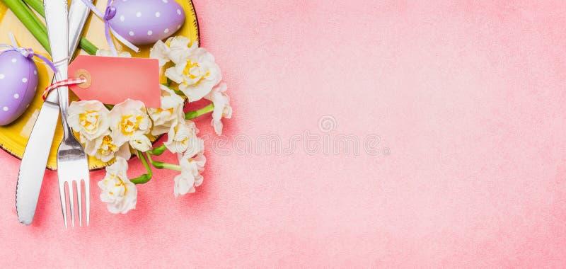 Regolazione di posto della tavola di Pasqua con i fiori della molla, le uova della decorazione e la coltelleria su fondo rosa-chi fotografia stock libera da diritti
