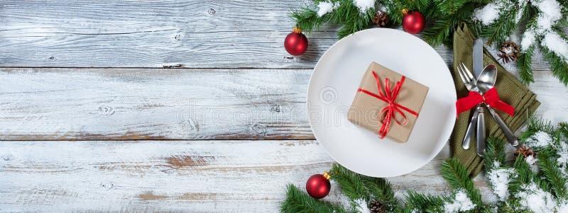 Regolazione di posto della tavola di Natale con il regalo sul piatto immagine stock libera da diritti