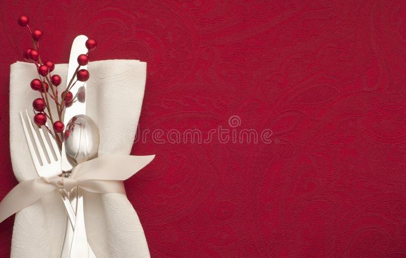 Regolazione di posto di Natale con Sterling Silverware in tovagliolo ed in nastro bianchi su fondo rosso con lo spazio della copia fotografie stock