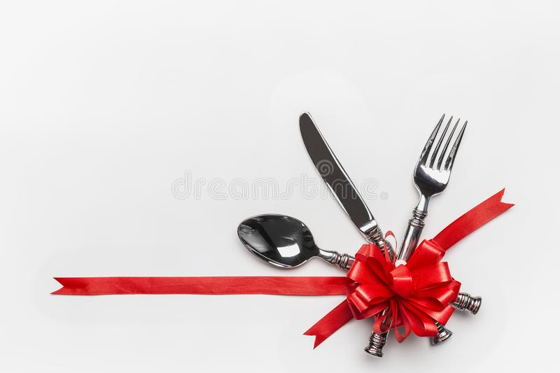 Regolazione di posto festiva della tavola con la coltelleria e l'arco rosso e nastro su fondo bianco, insegna Disposizione per la immagini stock