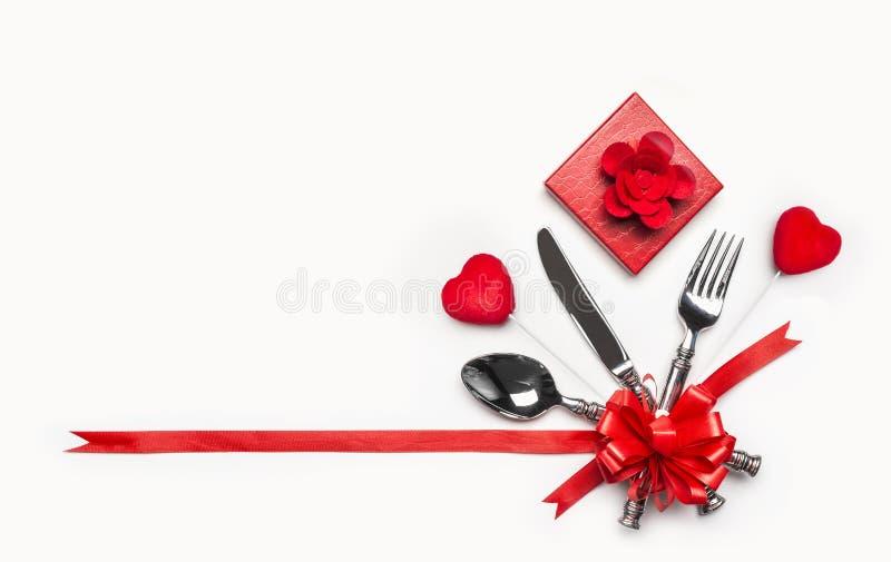 Regolazione di posto festiva della tavola con la coltelleria ed arco e nastro rosso, contenitore di regalo e cuori su fondo bianc fotografia stock