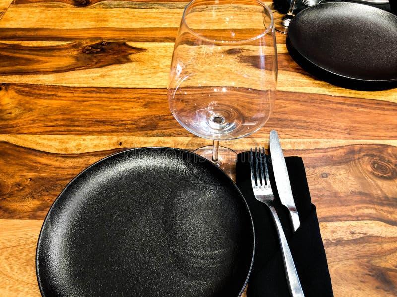 Regolazione elegante della tavola facendo uso di un vetro, dei piatti, dei tovaglioli con una forcella e del coltello fotografie stock libere da diritti