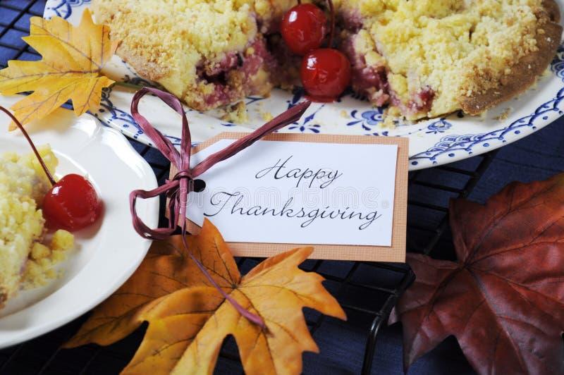 Regolazione felice della tavola di ringraziamento con la torta della briciola della mela di ciliegia - primo piano fotografia stock