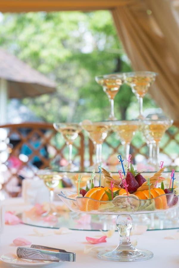 Regolazione festiva della tavola con la frutta ed i bicchieri di vino con champagne Decorazione di cerimonia nuziale immagine stock