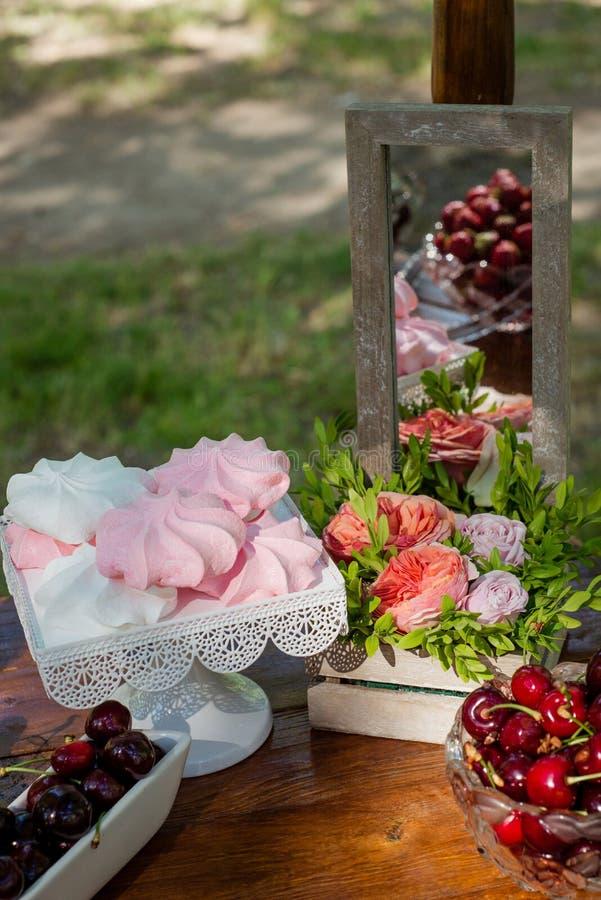 Regolazione festiva della tavola con la frutta, le caramelle gommosa e molle ed i fiori immagine stock