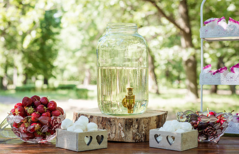 Regolazione festiva della tavola con la frutta, le caramelle gommosa e molle ed il succo della betulla all'aperto fotografie stock